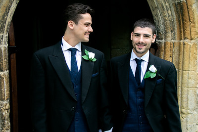 Smiling gay grooms dressed in suits leaving church after getting married