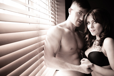 Sepia portrait of topless couple standing by window and blinds with both looking at camera