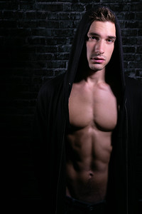 Portrait of handsome young man looking at camera with open black hoodie revealing muscular pecs and sixpack abs
