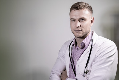 Handsome doctor with stethoscope and folded arms looking at camera