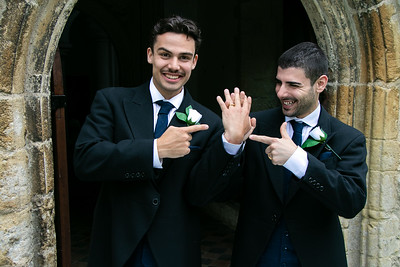 Gay couple laughing and smiling and they leave church after getting married, pointing at each other's rings