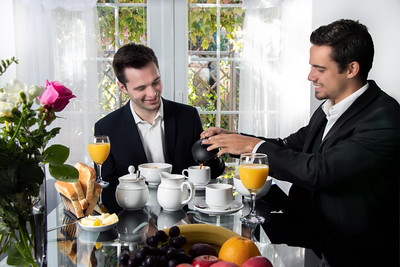 Friends or Gay couple sitting at table in front of patio doors eating breakfast and smiling