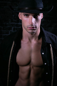 Portrait of handsome cowboy looking at camera wearing hat with open black shirt revealing defined pecs and sixpack abs