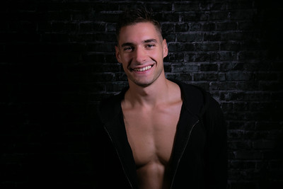 Portrait of handsome smiling young man looking at camera with open black shirt revealing muscular pecs and sixpack abs