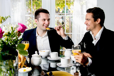 Friends or Gay couple sitting at table in front of patio doors eating breakfast in their suits