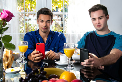 Friends or Gay couple sitting at breakfast table in front of patio doors looking at their mobile devices.