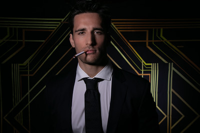 Portrait of handsome man in suit and tie in front of art deco backdrop with cigarette hanging from his lips