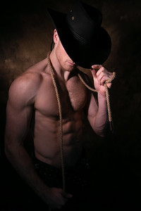 Shirtless cowboy wearing hat covering his face, holding rope around his neck with defined pecs and muscular sixpack abs