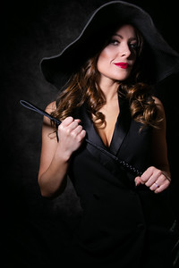 Colour portrait of beautiful female looking at camera wearing a floppy hat and holding a whip