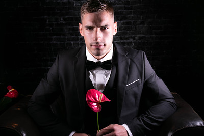 Portrait of handsome man wearing tuxedo with bowtie holding a flower and scowling at camera