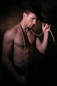 Handsome cowboy wearing a hat with barechest showing defined pecs and sixpack abs, muscular arms holding onto rope
