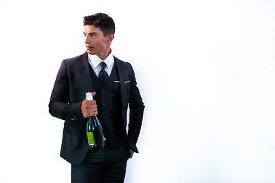 Good looking man in suit holding bottle of sparkling wine in front of white wall with plenty of room for copy