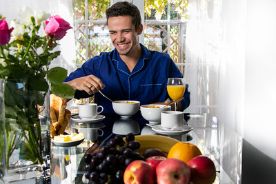 Happy smiling man in his pijamas having breakfast at table in front of patio doors with view of garden.