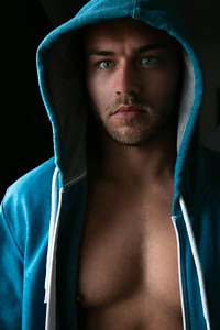 Portrait of handsome young man standing next to window with blue eyes, open hoodie revealing defined pecs