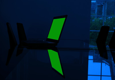 Laptop computer on glass desk in empty dark room with rain spattered window and green screen for own copy or graphic