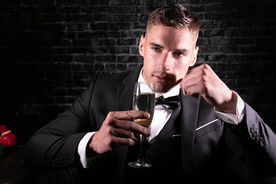 Portrait of handsome stylish man wearing a tuxedo holding up glass of sparkling wine and looking at camera.