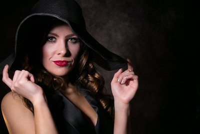 Colour portrait of beautiful female looking at camera holding her floppy hat on her head
