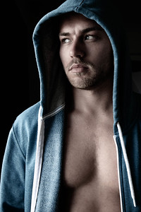 Handsome young man standing next to window with blue eyes, open hoodie revealing defined pecs
