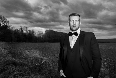 Handsome man wearing tuxedo standing with fields and stormy sky behind him.