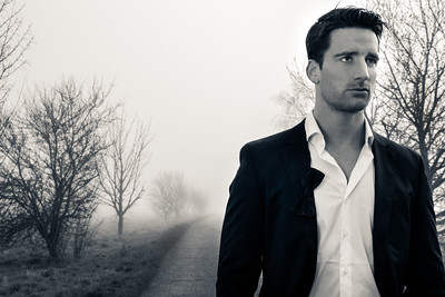 Handsome man wearing suit walking on a lonely foggy road