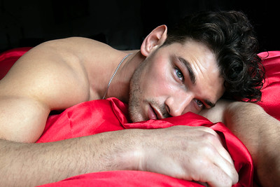 Handsome man lying shirtless on bed looking away from camera