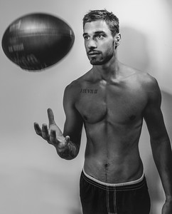 Black and white portrait of young attractive topless muscular man with beard tossing american football