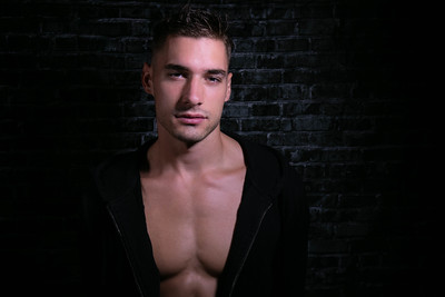 Portrait of handsome serious young man looking at camera with open black shirt revealing muscular pecs and sixpack abs