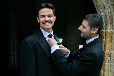 Gay couple laughing outside of church with one groom adjusting his husband's tie