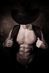 Attractive cowboy wearing hat covering his face opening waistcoat to reveal defined pecs and muscular sixpack abs