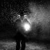 Man standing in front of strong light in rain