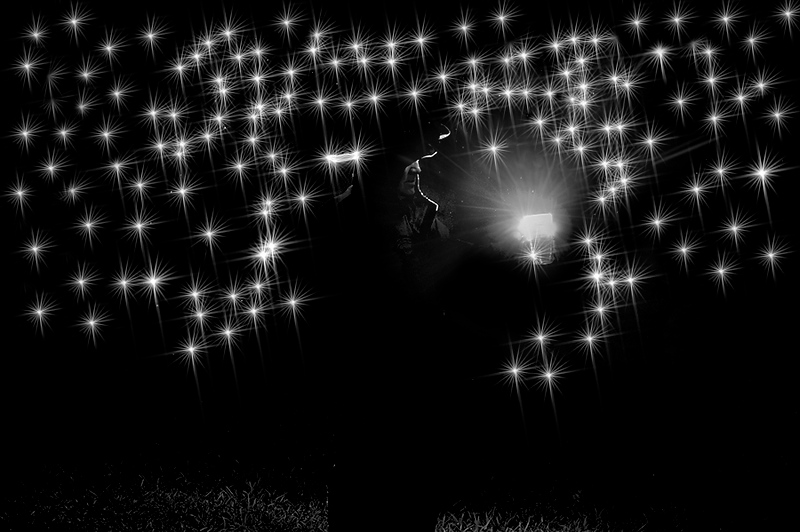 Man in front of direct light at night with stars