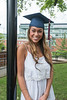 Woman graduates in graduation hat outside smiiling