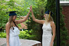 Two woman gradustes in caps doing high five