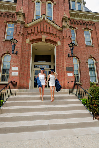 Two woman graduates walking down steps infront of building