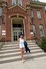 Woman graduate walking down steps in front of building