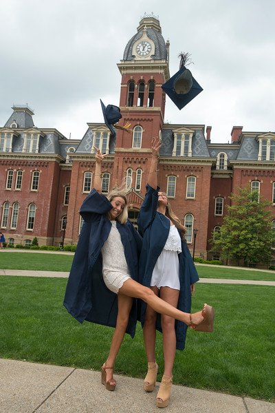 Two woman graduates tossing their graduation caps in the air