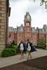 Two woman graduates walknig down the path