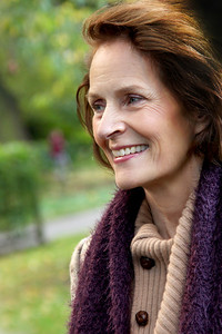 Mature lady in her 50s or 60s in the park in autumn.