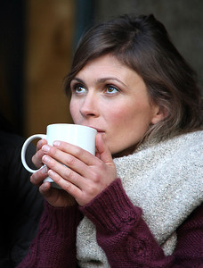 Girl holding coffee mug looking up with a thoughtful/dreaming expression