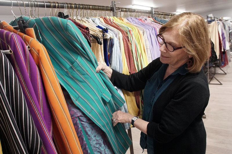 """BEN GARVER — THE BERKSHIRE EAGLE<br /> Barrington Stage Company (BSC) Artistic Director Julianne Boyd browses costumes from the Broadway production of """"On the Town."""""""