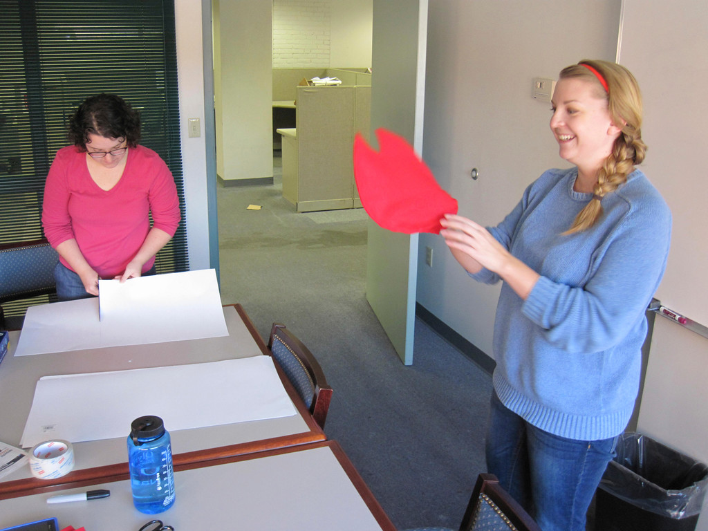 . Eagle features editor Lindsey Hollenbaugh (left) and online editor Laura Lofgren (right) work on creating a do-it-yourself \'Lobster-in-a-Pot\' costume for last week\'s Third Thursday festival. Jenn Smith/Berkshire Eagle Staff Oct. 18, 2013