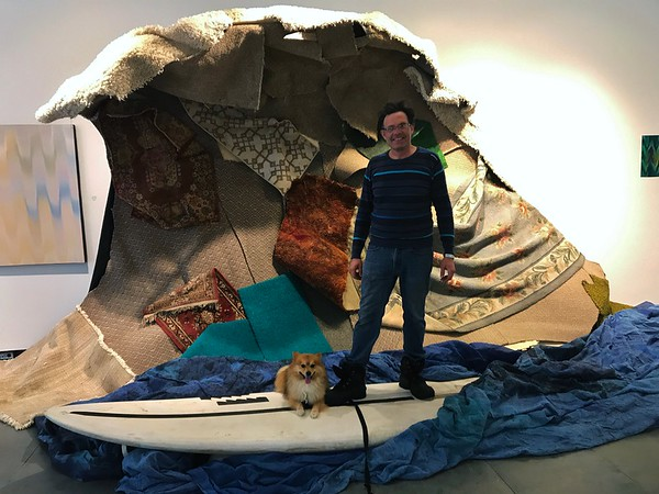 """JENNIFER HUBERDEAU — THE BERKSHIRE EAGLE<br /> Artist Henry Klein catches a ride on """"Carpet Wave,"""" an installation piece made with commercial carpet pieces."""