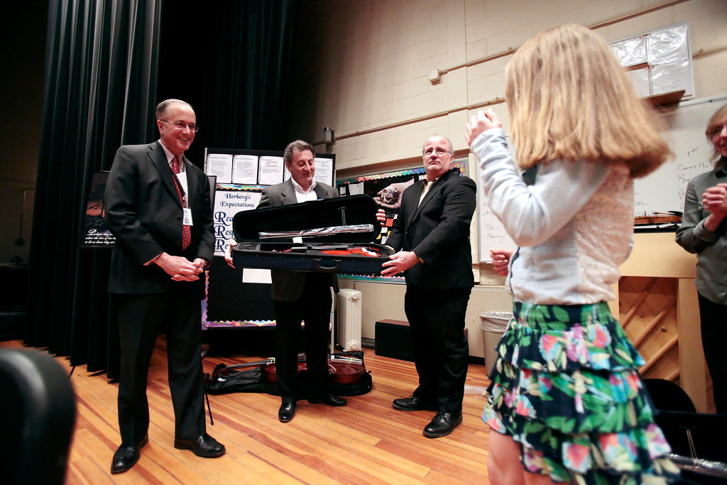 . Karissa Yzerman-Gleason walks up to accept her violin from Mayor Daniel Bianchi, left, Domenic Izzi, center, and Mike Fillipi, as one of six Herberg Middle School students to receive musical instruments from the Domenic A. Izzi Jr. Foundation for Young Aspiring Musicians. Thursday, April 3, 2014. Stephanie Zollshan / Berkshire Eagle Staff / photos.berkshireeagle.com