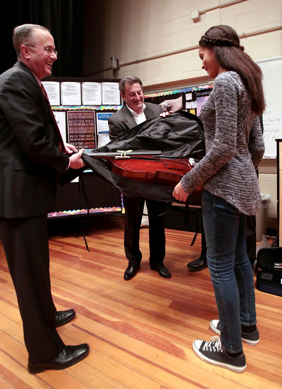 . Kamea Quetti accepts her violin from Mayor Daniel Bianchi, left, and Domenic Izzi as one of six Herberg Middle School students to receive musical instruments from the Domenic A. Izzi Jr. Foundation for Young Aspiring Musicians. Thursday, April 3, 2014. Stephanie Zollshan / Berkshire Eagle Staff / photos.berkshireeagle.com