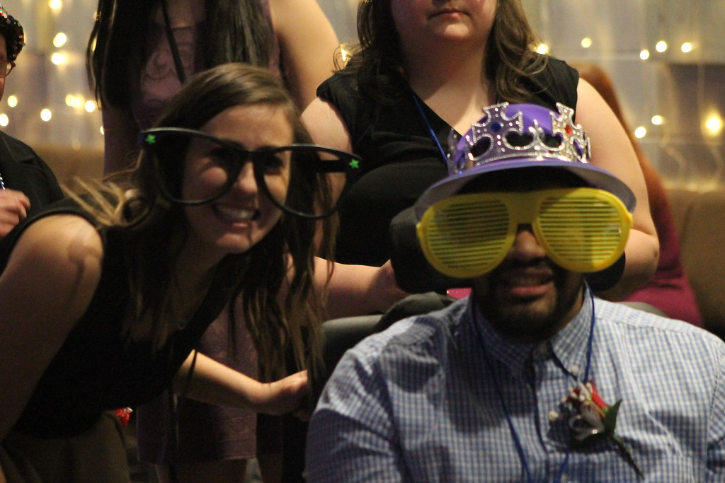 . Prom goers play with props as they wait thier turn line for the photo booth at the Night to Shine Prom held by Painesville Baptist Church, Feb. 9.