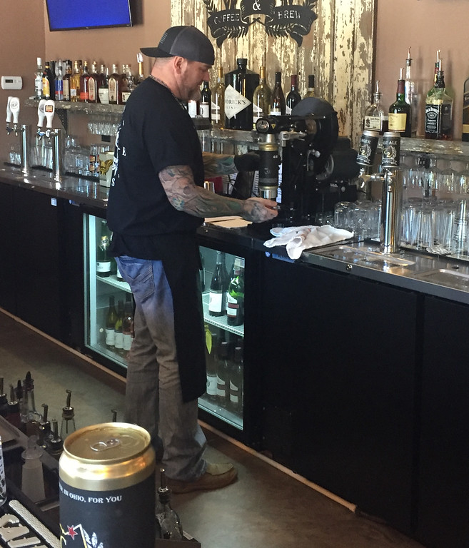 . Brian Richards, co- owner of the new 1922 Coffee and Brew in Painesville Township, uses a crowler on June 14. 1922 Coffee and Brew customers can purchase 32 oz. cans of fresh craft beer to go because of the crowler. (Tawana Roberts)