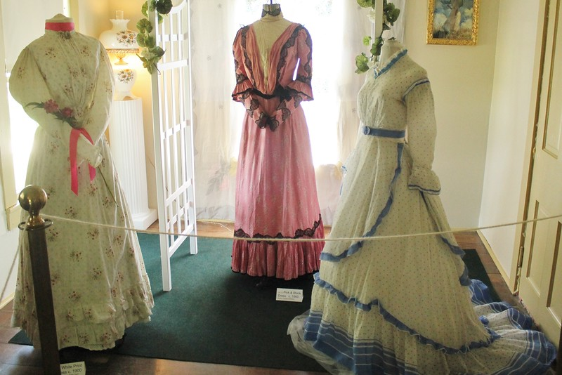 Left: dress worn by wife of Issac Dyer, white cotton, red flower print, tight fitted bodice, skirt with flat front  and gathered back, early modest leg-o-mutton sleeves. c 1890-1985. Center: Black and pink printed dress. Right. four piece dress also worn by Mrs. Issac Dryer, separate  bodice, skirt, layer of apron front, with peplum back and belt. Right:  white cotton lawn with blue polka dot. sleeves are straight and drop at shoulder with wide ruffled cuffs and long train. 1865-1870 {Photo by Kristi  Garabrandt-The News-Herald}