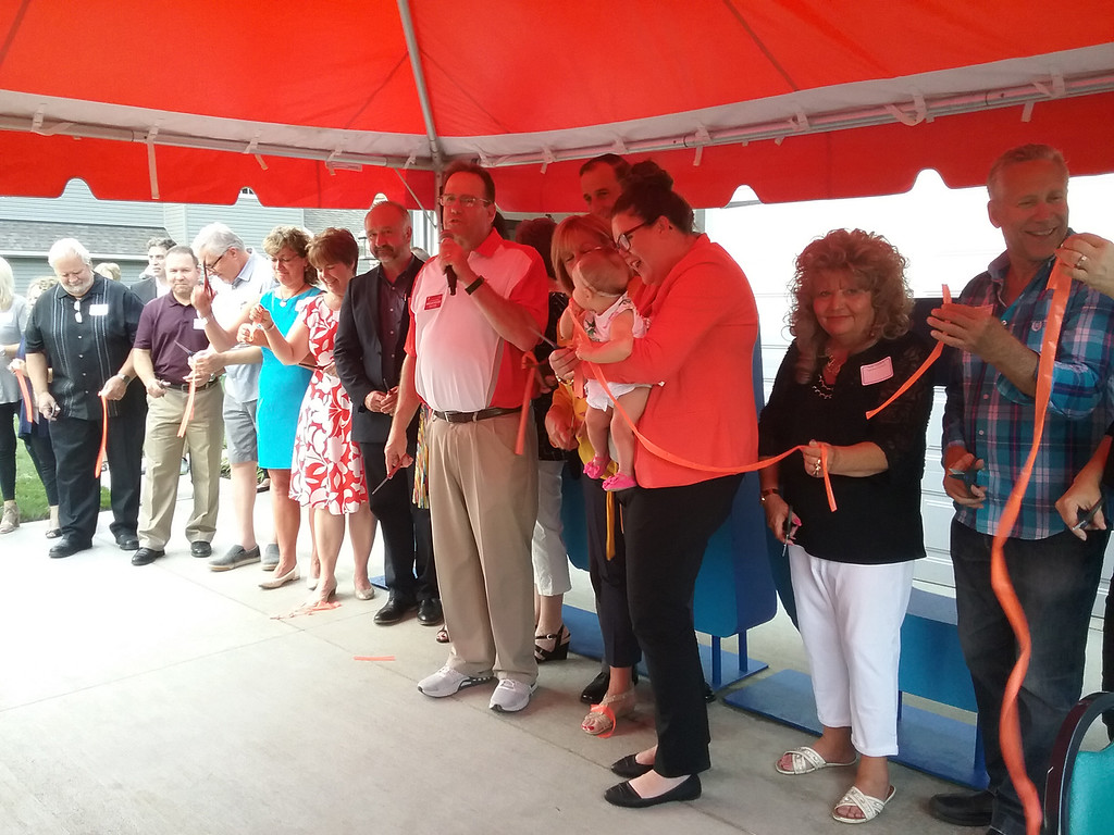 . YMCA officials, builders, designers and others associated with the Dream House gathered together for a ribbon cutting on June 22 to officially mark the home\'s completion. (Jean Bonchak - The News-Herald)