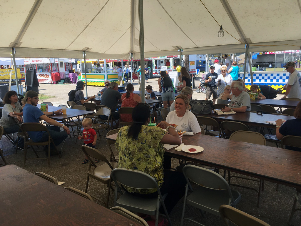 . Bill DeBus � The News-Herald <br> People enjoy their meals in a tent on July 27 at the Lake County Fair.