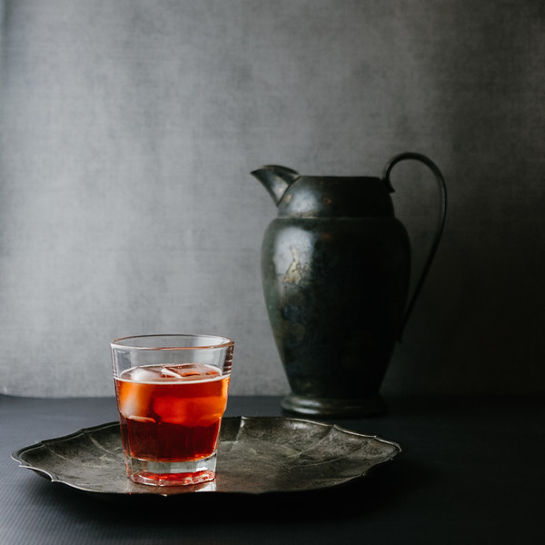 Moody red cocktail with gray pitcher in the background